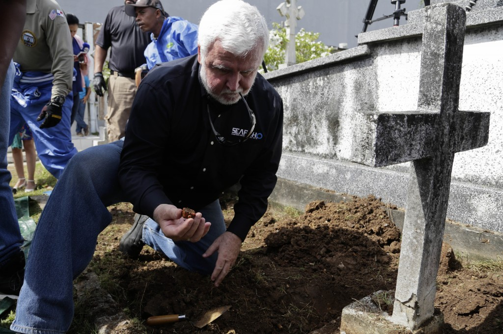 Maritime archaeologist James Delgado inspects debris on the grave site of Julius H. Kroehl before exhuming his body from Amador Cemetery in the Chorri