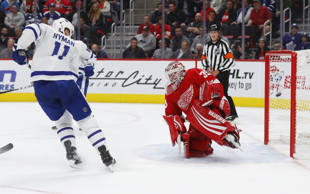 Toronto Maple Leafs center Zach Hyman (11) watches a Morgan Rielly shot go in for a goal on Detroit Red Wings goaltender Jimmy Howard (35) during the