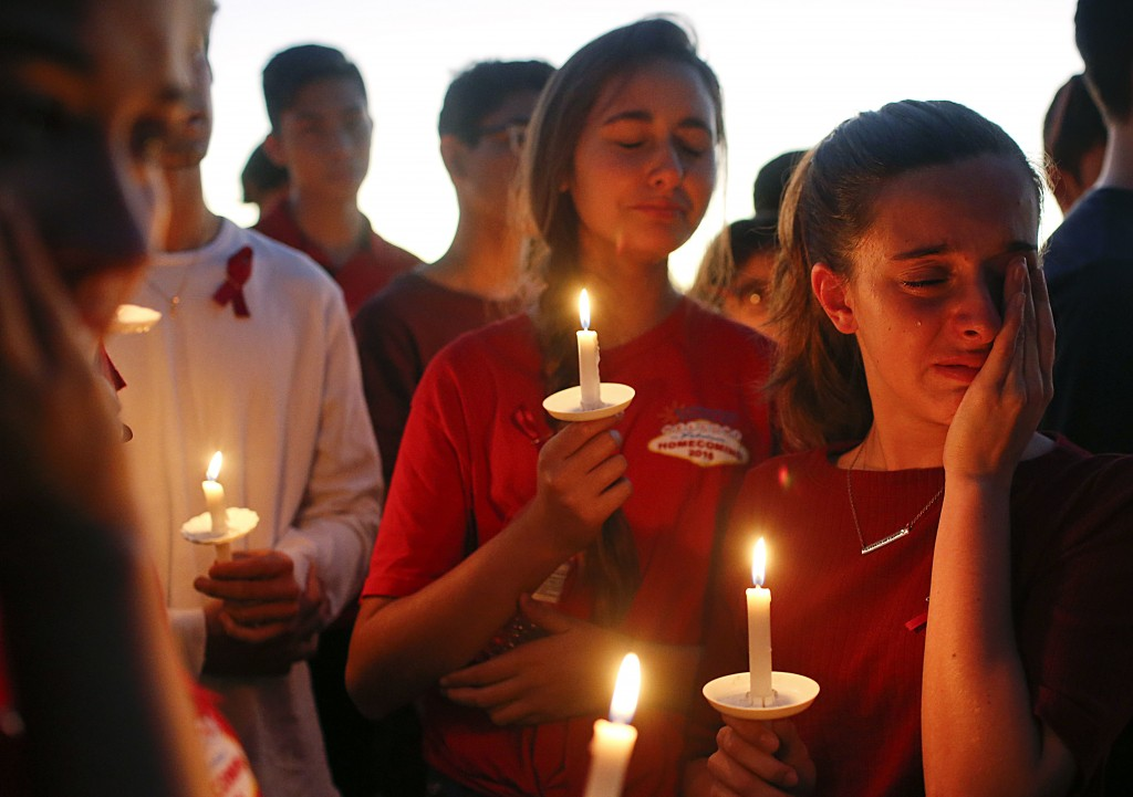 FILE - In this Feb. 15, 2018, file photo, ttudents gather to grieve during a vigil at Pine Trails Park for the victims of a shooting at Marjory Stonem