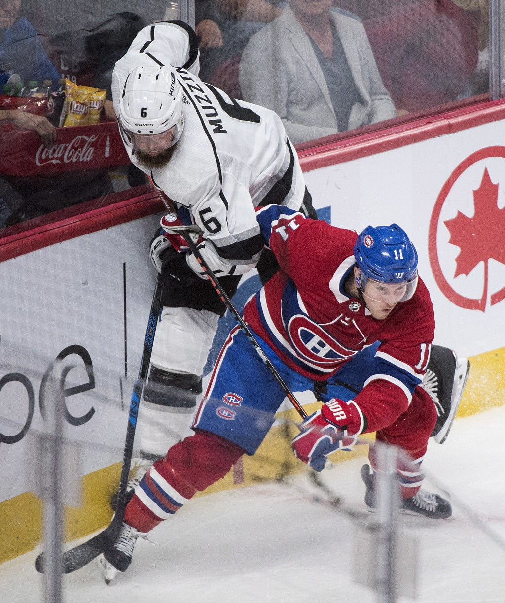 Los Angeles Kings' Jake Muzzin, left, collides with Montreal Canadiens' Brendan Gallagher during the first period of an NHL hockey game Thursday, Oct.