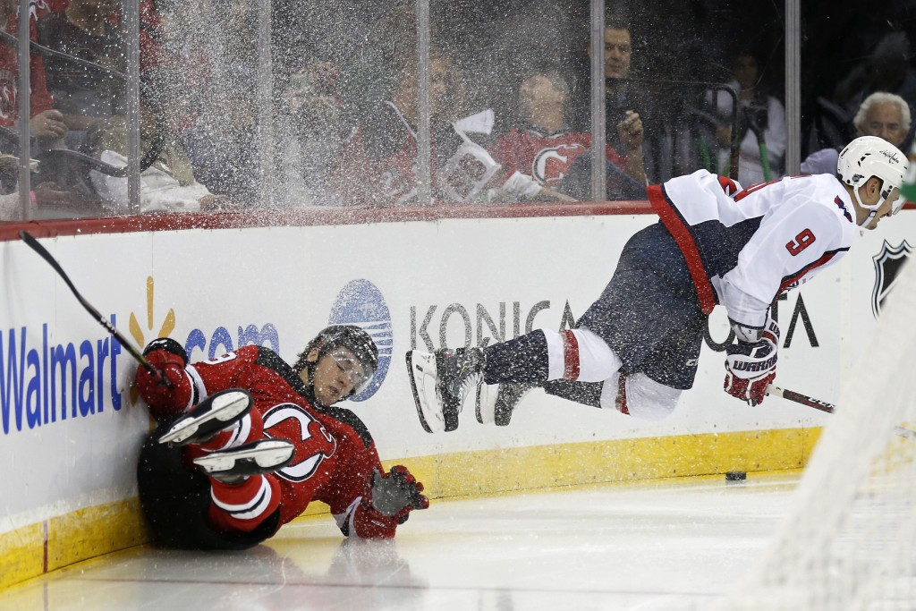 New Jersey Devils' Nico Hischier crashes into the boards while battling for the puck with Washington Capitals' Dmitry Orlov (9) during the second peri