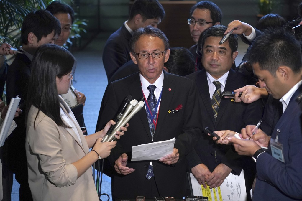 Okinawa Governor Denny Tamaki, center, speak to journalists after meeting with Japanese Prime Minister Shinzo Abe at Abe's office in Tokyo Friday, Oct