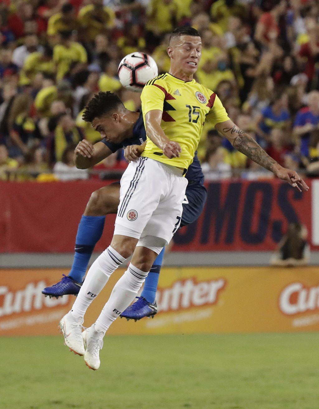 Colombia midfielder Mateus Uribe (15) goes up for a header against United States' Antonee Robinson, left, during the first half of an international fr