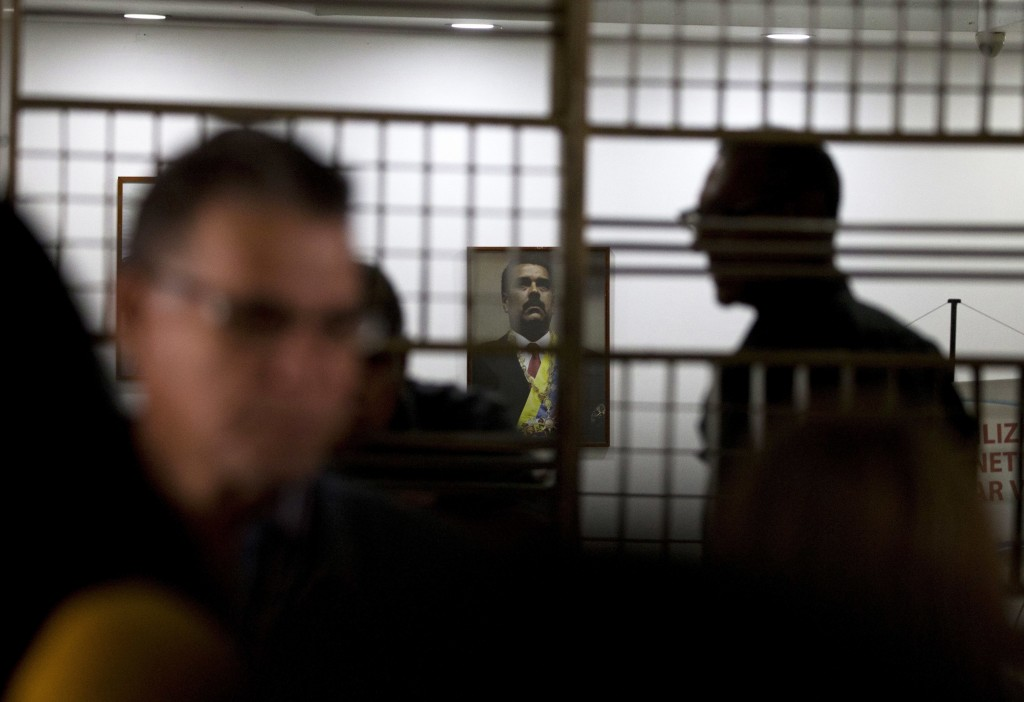 In this Friday, Oct. 5, 2018 photo, a framed image of Venezuela's President Nicolas Maduro hangs above a main desk of the Labor Ministry while workers