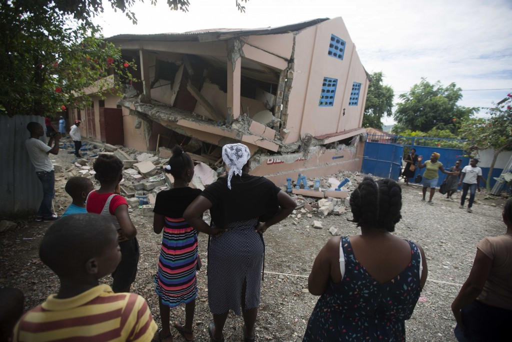 In this Sunday, Oct. 7, 2018 photo, residents stand looking at a collapsed school damaged by a magnitude 5.9 earthquake the night before, in Gros Morn