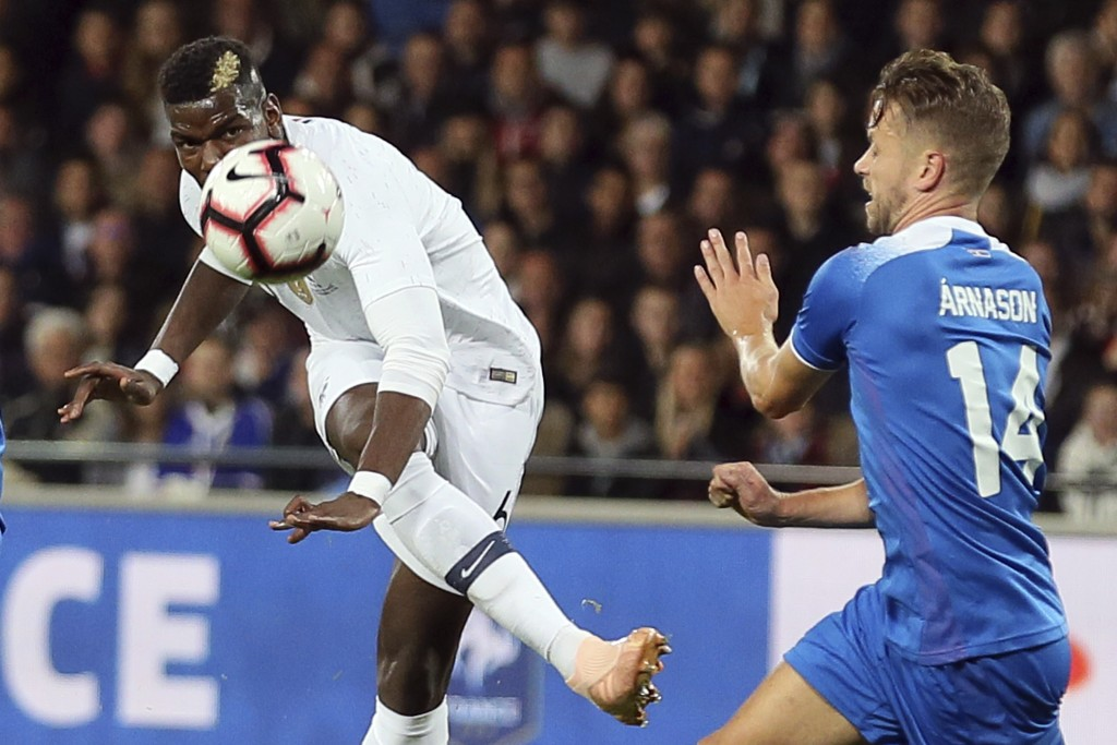 France's Paul Pogba, left, kicks the ball during a friendly soccer match between France and Iceland, in Guingamp, western France, Thursday, Oct. 11, 2