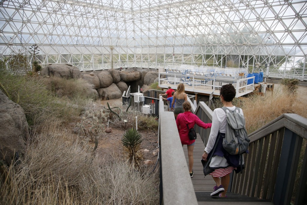 In this Friday, July 31, 2015, photo, tourists walk through the enclosed coastal fog desert ecosystem of the Biosphere 2 in Oracle, Ariz. Biosphere 2