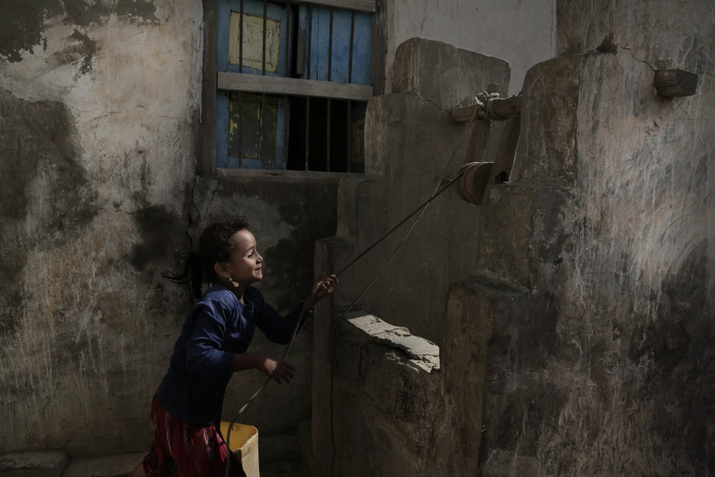 FILE - In this Feb. 12, 2018, file photo, a girl pulls water from a well in the home of Ahmed al-Kawkabani, leader of the southern resistance unit in