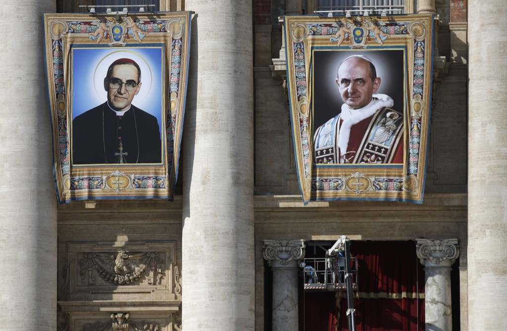 The tapestries of Roman Catholic Archbishop Oscar Romero, left, and Pope Paul VI hang from a balcony of the facade of St. Peter's Basilica at the Vati