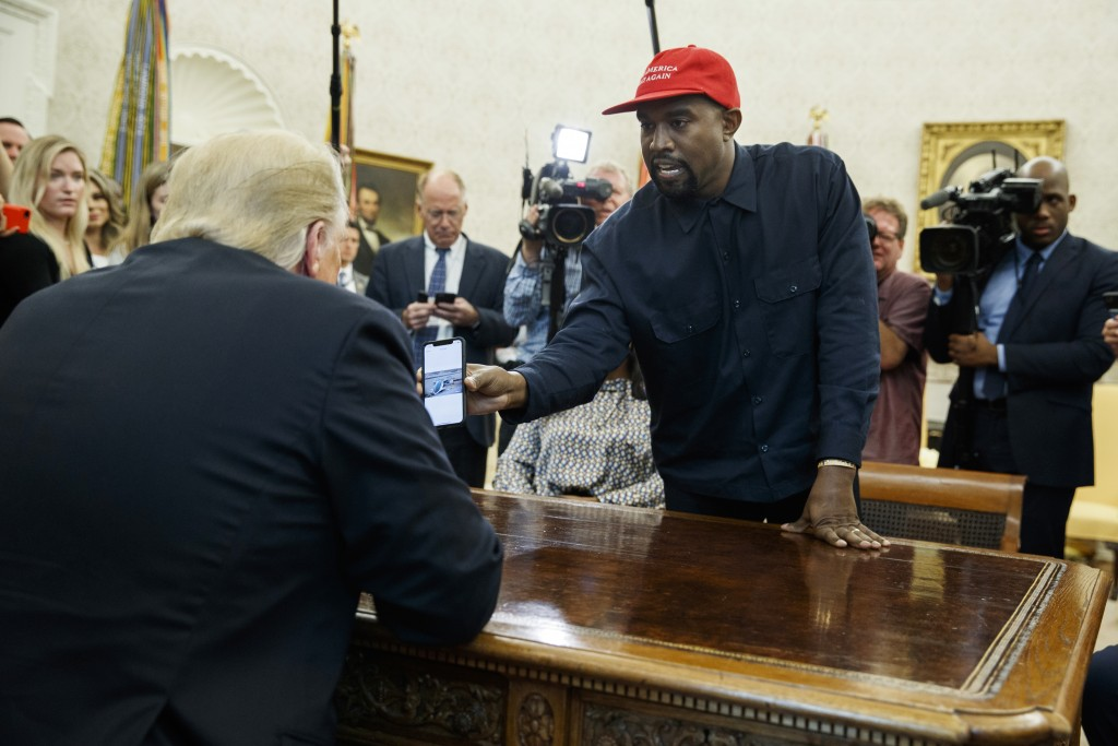 Rapper Kanye West shows President Donald Trump a photograph of a hydrogen plane during a meeting in the Oval Office of the White House, Thursday, Oct.