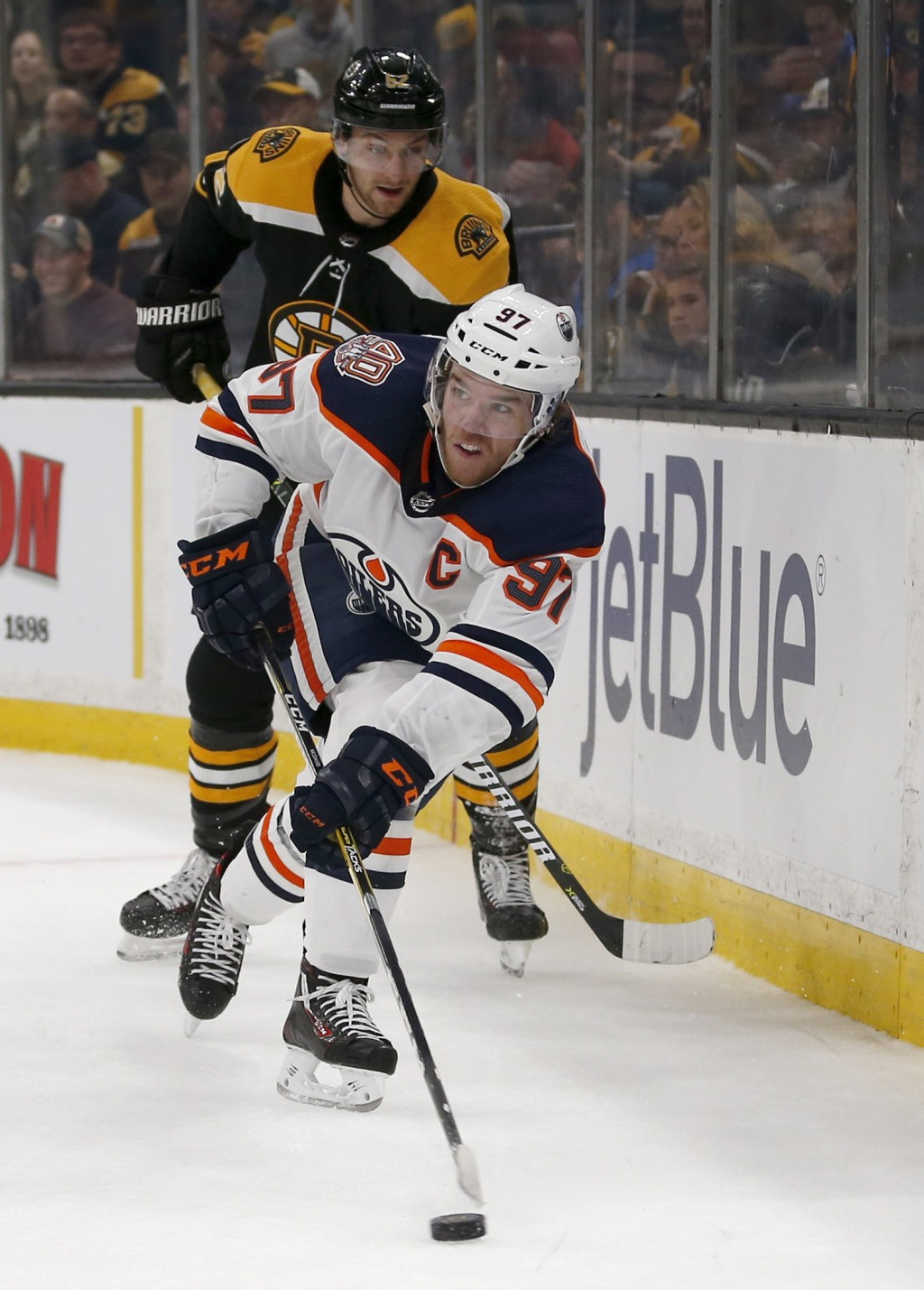 Edmonton Oilers center Connor McDavid (97) passes the puck from behind the net as Boston Bruins center Sean Kuraly (52) gives chase during the first p