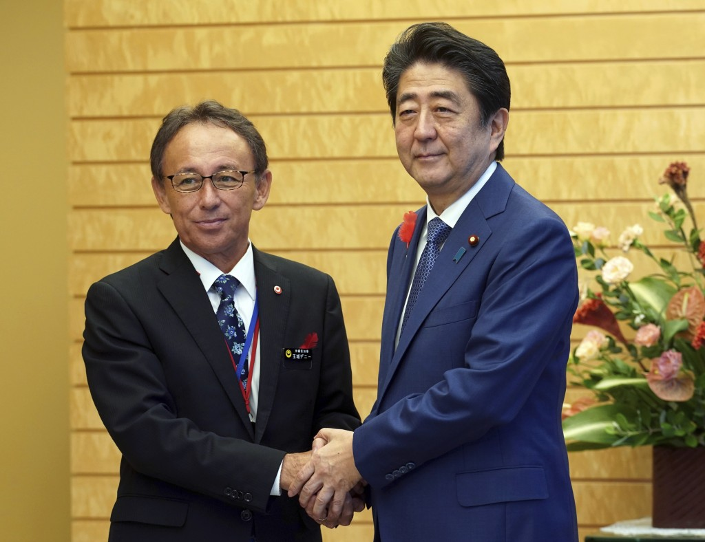 Okinawa Governor Denny Tamaki, left, and Japanese Prime Minister Shinzo Abe shake hands during a meeting at Abe's office in Tokyo Friday, Oct. 12, 201