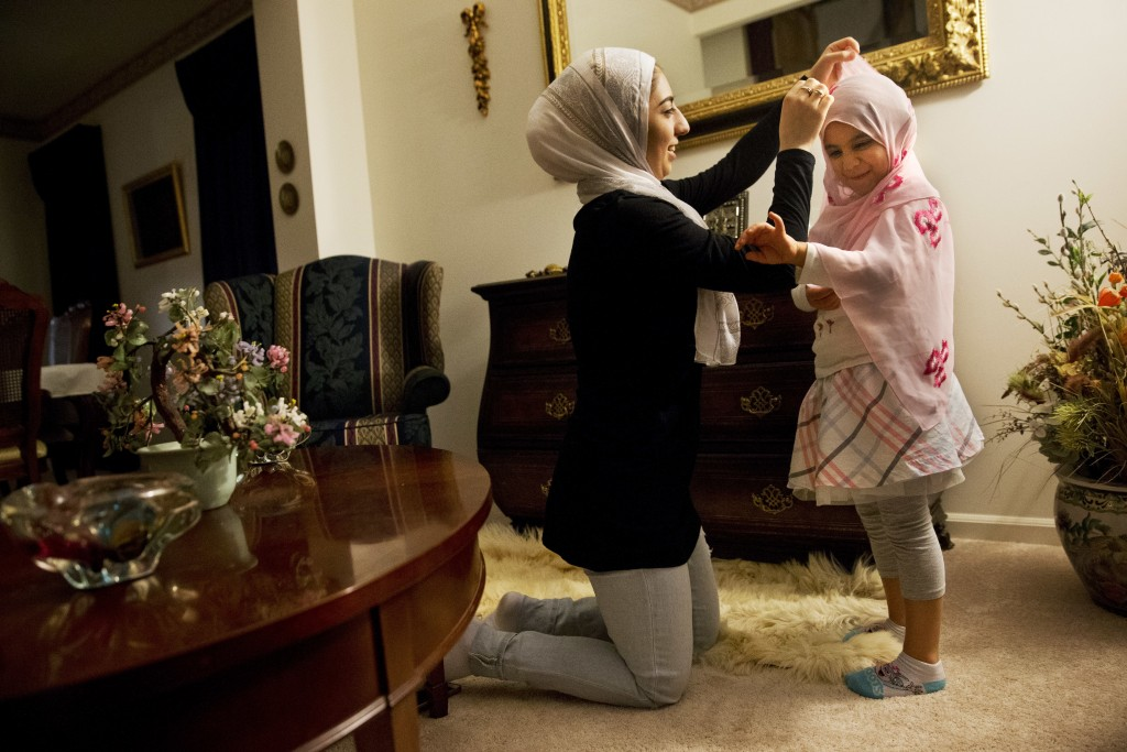ILE - In this May 6, 2016, file photo, Hannah Shraim, 17, left, fixes a scarf around Lana Algamil, 5, after the little girl asked Hannah if she could