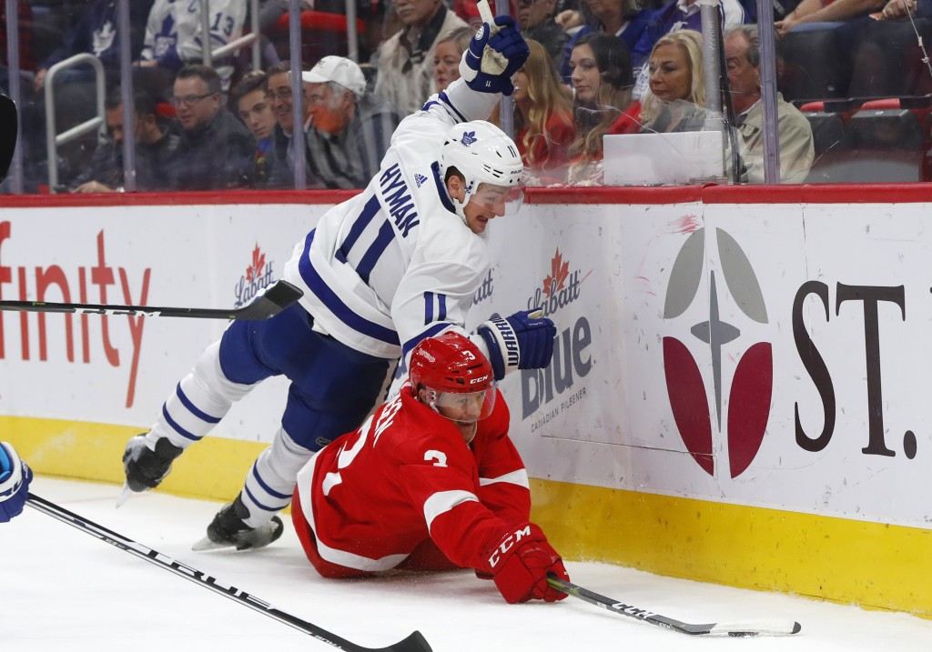 Toronto Maple Leafs center Zach Hyman (11) and Detroit Red Wings defenseman Nick Jensen (3) battle for the puck during the first period of an NHL hock