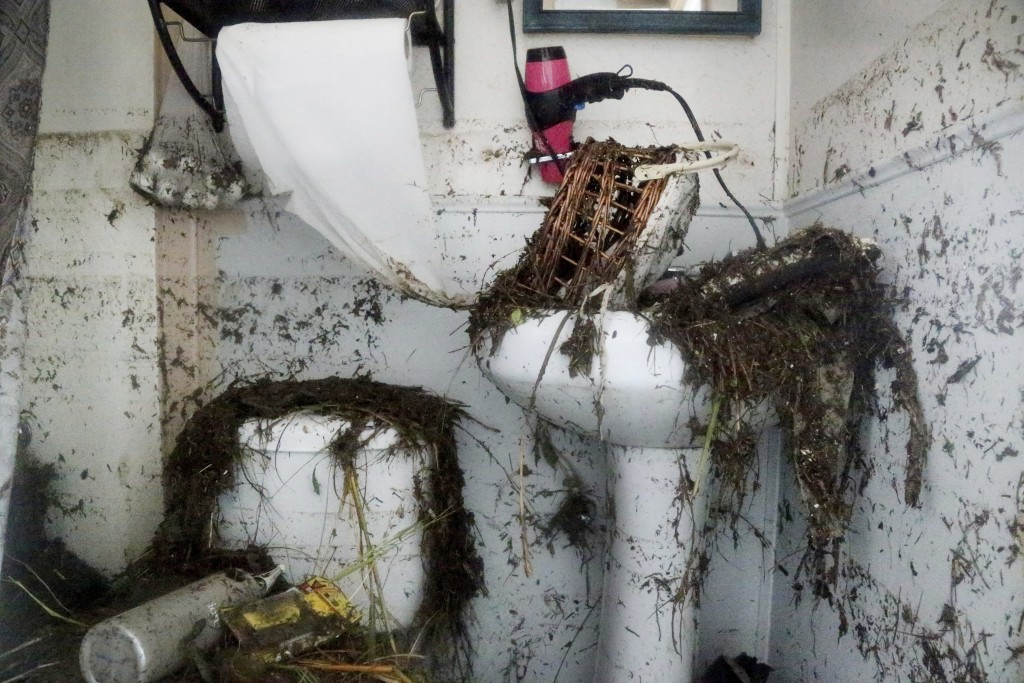 The restroom in the home of Cindy an James Murphy, in Port St. Joe, Fla., is plastered with the remnants of a violent tidal surge on Thursday , Oct. 1