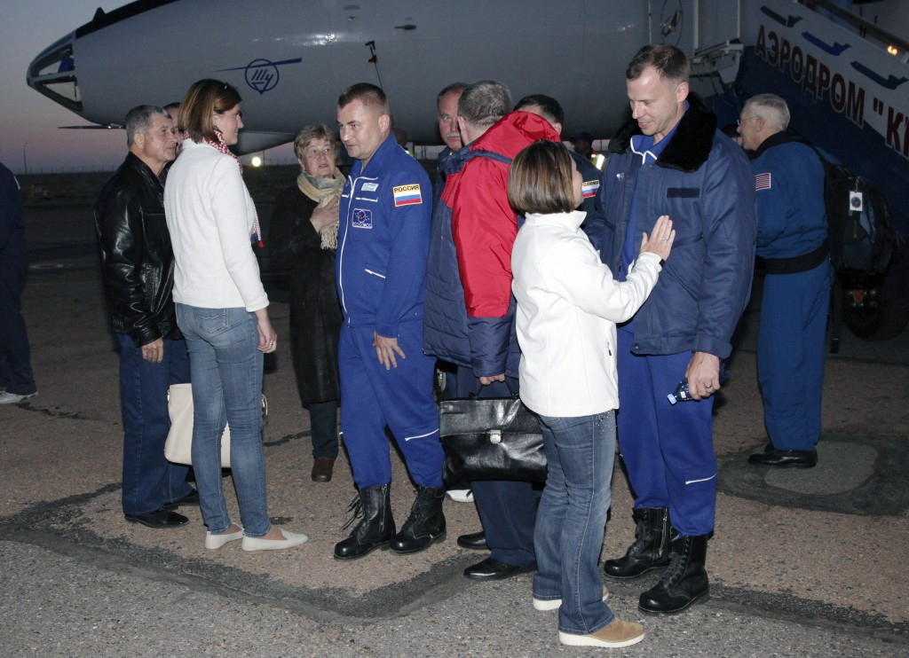 In this photo provided by Roscosmos, Russian cosmonaut Alexey Ovchinin, center, and U.S. astronaut Nick Hague, second from right, meet with their fami
