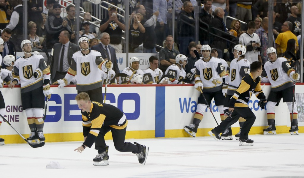 Pittsburgh Penguins ice crew members pick up hats on the ice as the Vegas Golden Knights lean along the boards after Penguins' Phil Kessel scored his