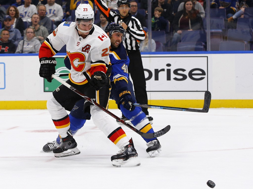 Calgary Flames' Sean Monahan, left, gets off a shot as he is pressured by St. Louis Blues' Robert Bortuzzo during the first period of an NHL hockey ga