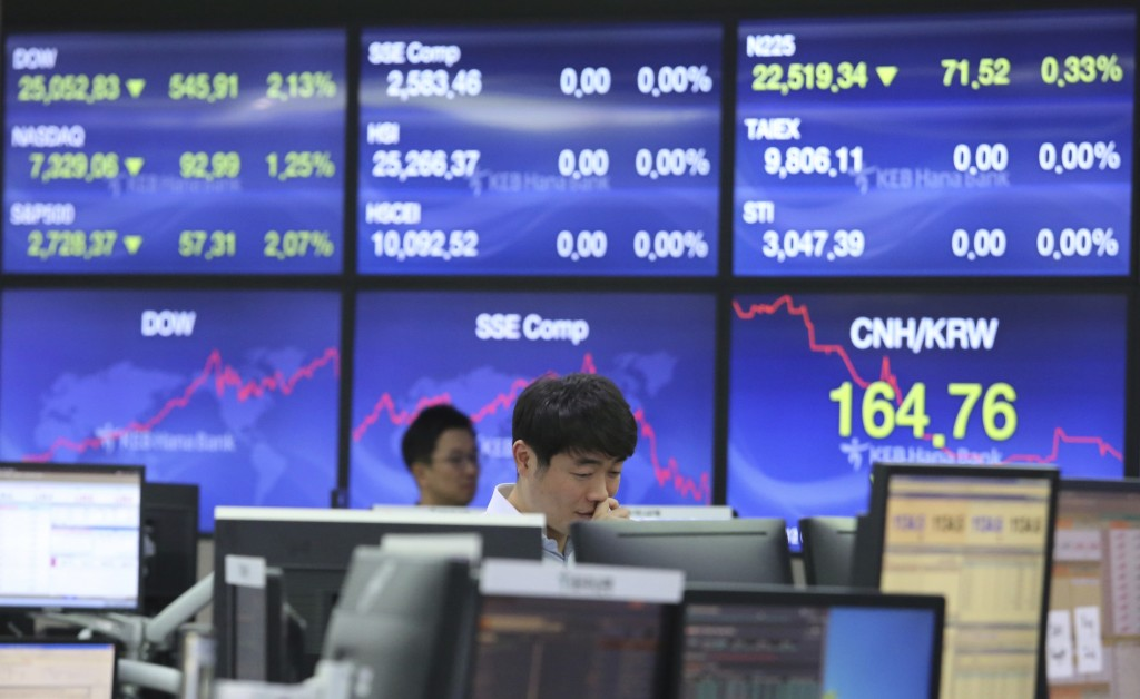 A currency trader watches monitors at the foreign exchange dealing room of the KEB Hana Bank headquarters in Seoul, South Korea, Friday, Oct. 12, 2018