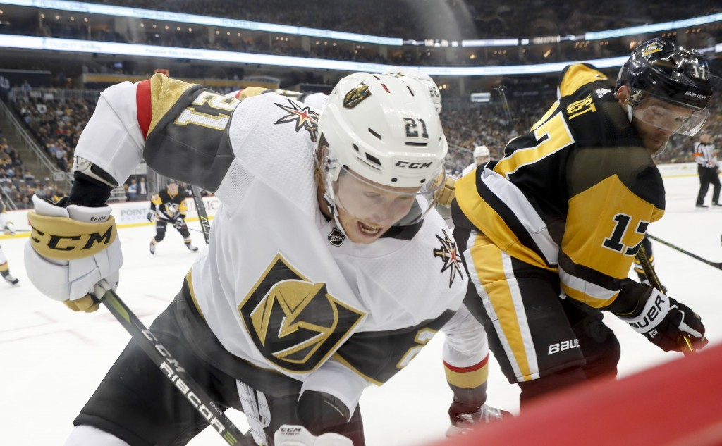 Vegas Golden Knights' Cody Eakin (21) and Pittsburgh Penguins' Bryan Rust battle along the boards during the second period of an NHL hockey game Thurs