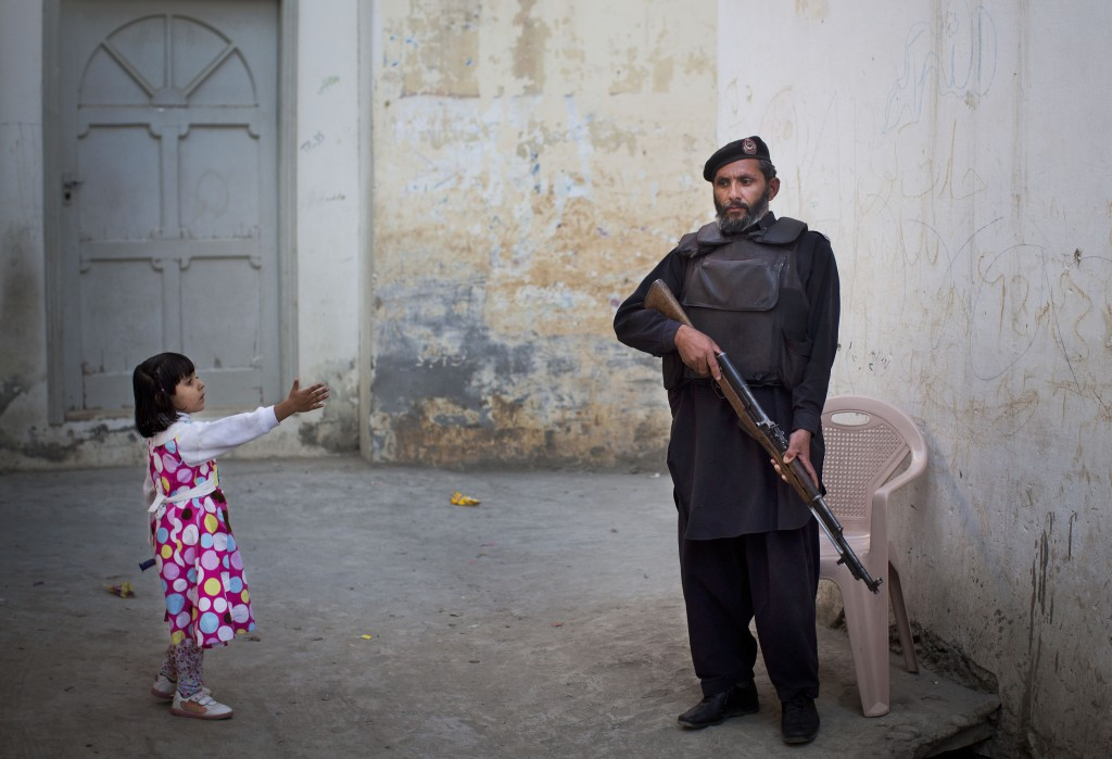 FILE - In this Wednesday, Nov. 15, 2012 file photo, a young girl in her colorful dress reaches out to greet a Pakistani policeman securing the road ou