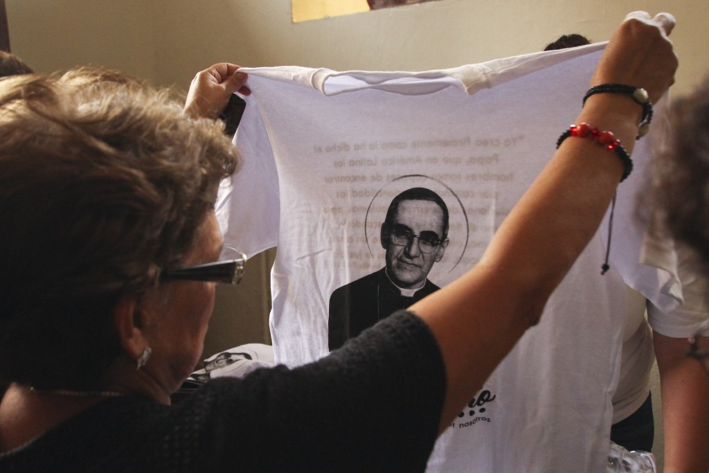 In this Oct. 7. 2018 photo, a woman checks out a shirt for sale with the image of the Archbishop Oscar Arnulfo Romero, at the entrance of the Metropol