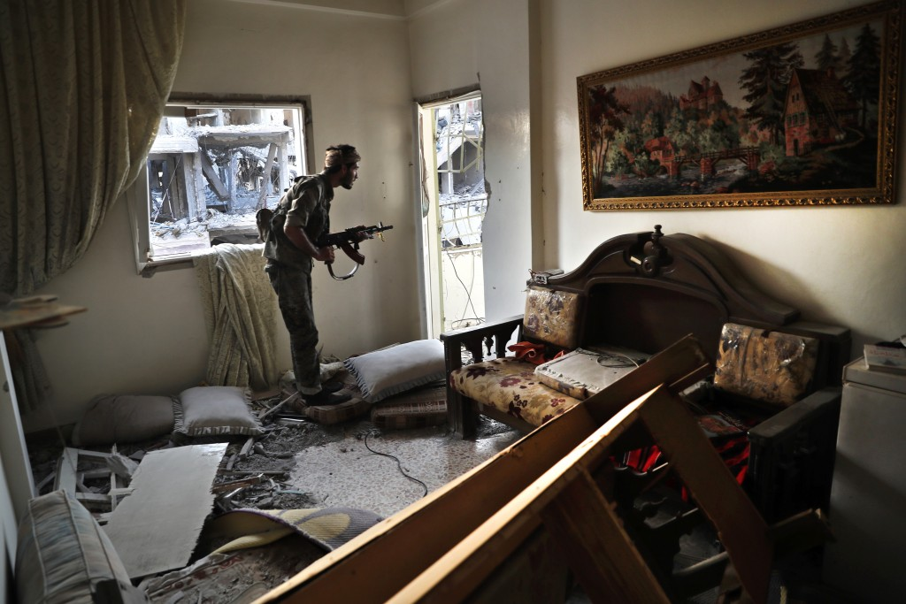 FILE - In this Thursday, July 27, 2017 file photo, a U.S.-backed Syrian Democratic Forces fighter, looks through a window as he takes his position ins