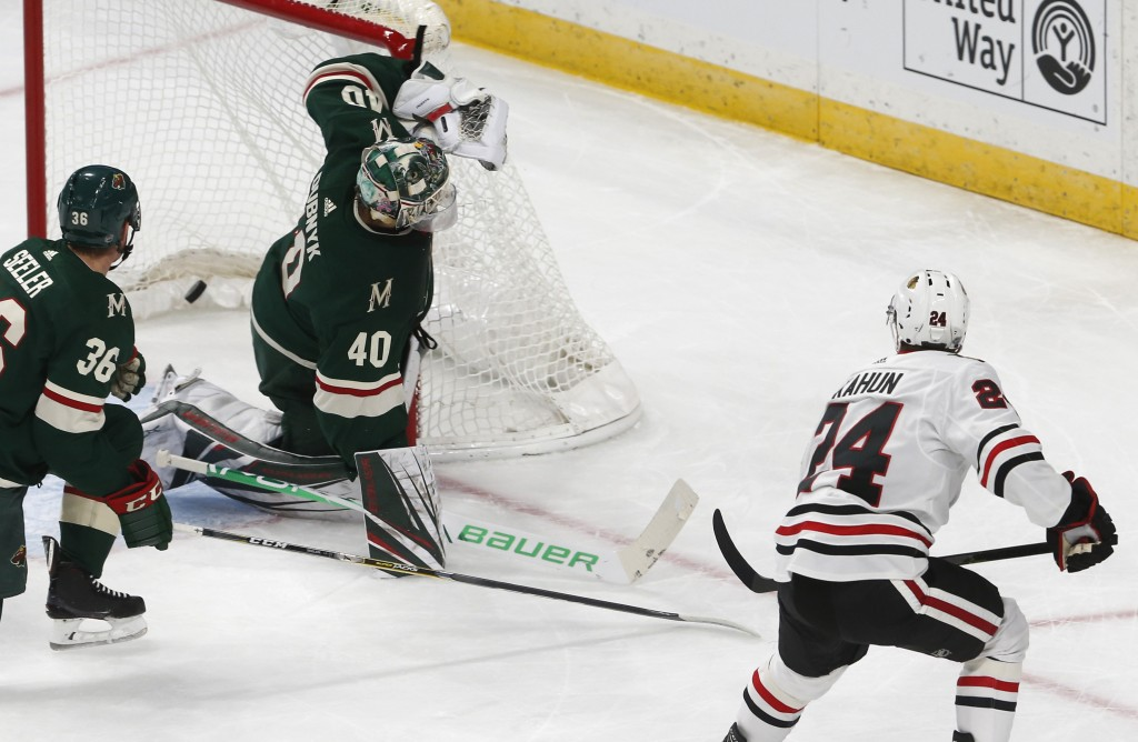 Chicago Blackhawks' Dominik Kahun, right, of the Czech Republic, scores a goal against Minnesota Wild goalie Devan Dubnyk during the first period of a