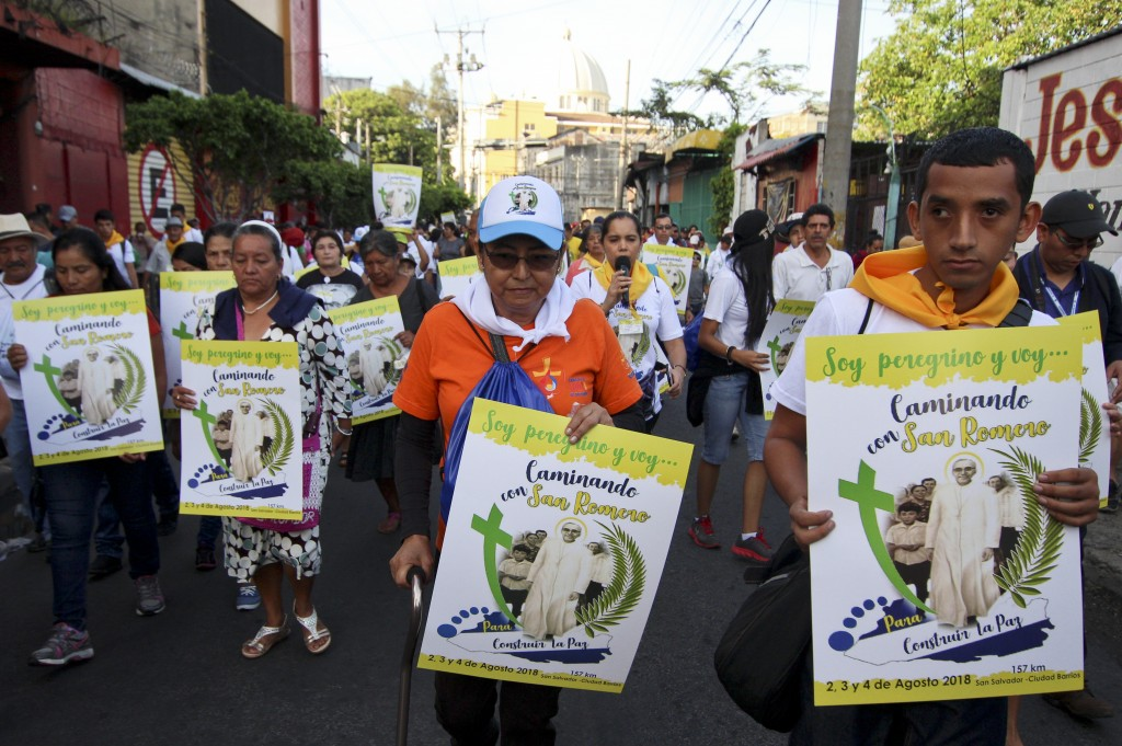 In this Aug. 2. 2018 photo, a group of pilgrims carrying posters to Archbishop Oscar Arnulfo Romero, take part in a religious procession in San Salvad