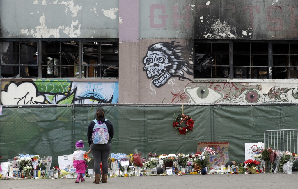 FILE - In this Dec. 13, 2016, file photo, flowers, pictures, signs and candles, are placed at the scene of a warehouse fire in Oakland, Calif. A judge