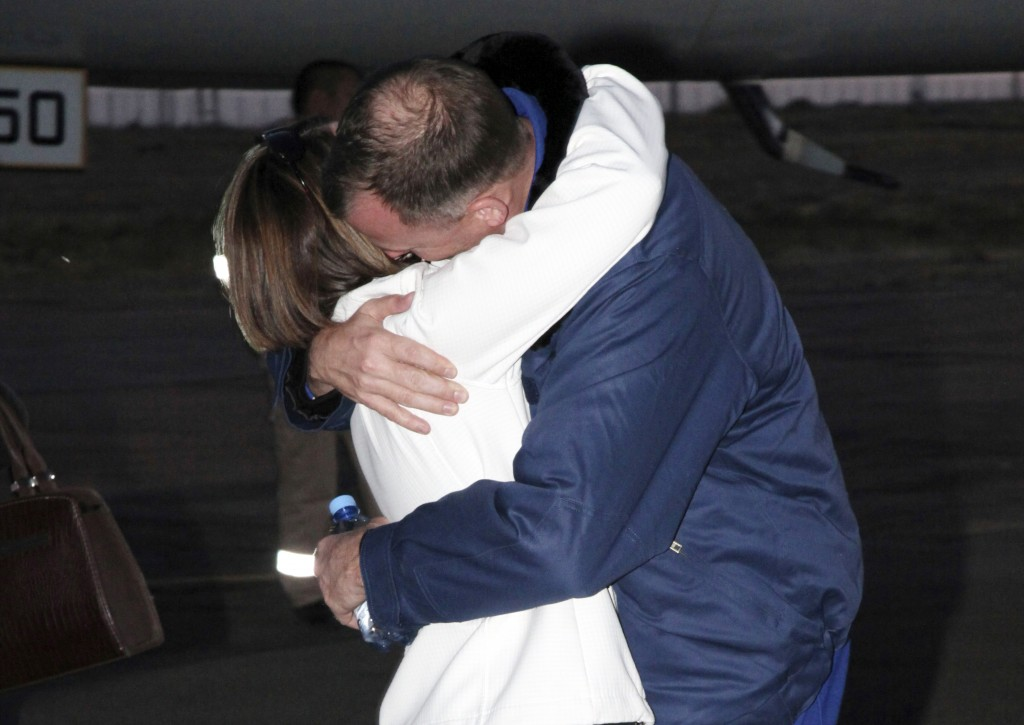 In this photo provided by Roscosmos, U.S. astronaut Nick Hague, right, embraces his wife Catie in Baikonur airport, Kazakhstan, Thursday, Oct. 11, 201