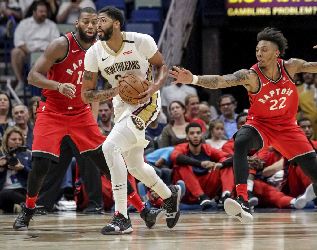 Toronto Raptors guard Malachi Richardson (22) reaches for the ball held by New Orleans Pelicans forward Anthony Davis (23) as Davis is guarded by Toro