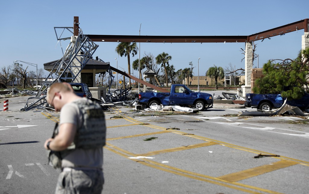A soldier stands guard at the damaged entrance to Tyndall Air Force Base in Panama City, Fla., Thursday, Oct. 11, 2018, in the aftermath of hurricane