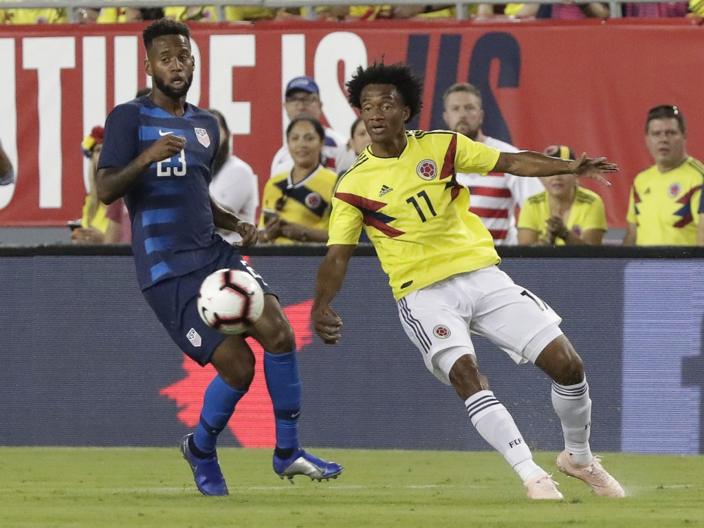 Colombia's Juan Cuadrado (11) moves the ball away from Unites States' Kellyn Acosta, left, during the first half of an international friendly soccer m