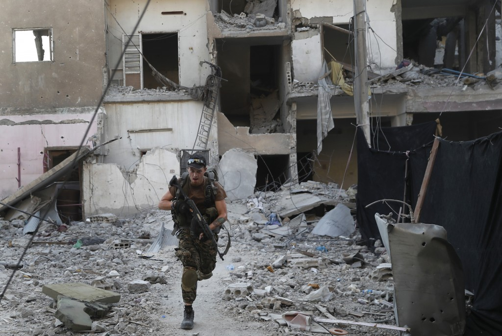FILE - In this Thursday, July 27, 2017, a U.S.-backed Syrian Democratic Forces fighter runs in front of a damaged building as he crosses a street on t