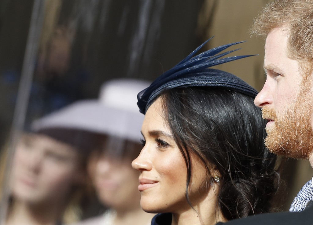 Prince Harry and his wife Meghan, Duchess of Sussex, smile as they wait for the bridal procession at the wedding of Princess Eugenie of York and Jack