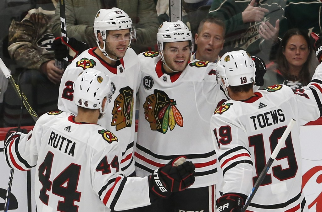 Chicago Blackhawks' Alex DeBrincat, second from right, is congratulated by teammates after scoring against Minnesota Wild goalie Devan Dubnyk during t