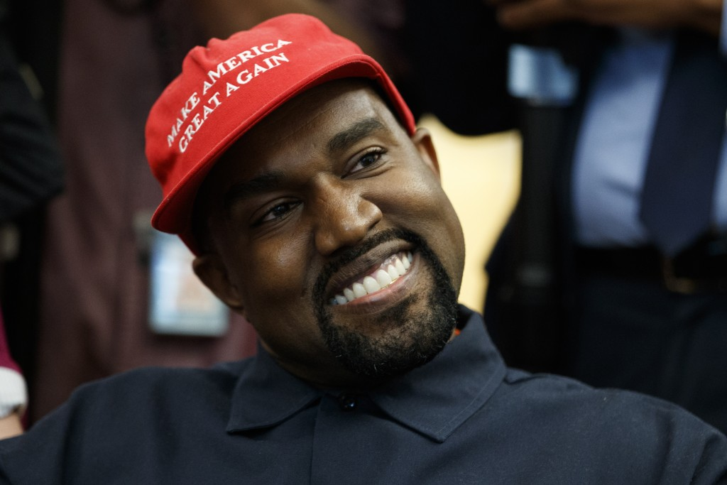 Rapper Kanye West smiles as he listens to a question from a reporter during a meeting in the Oval Office of the White House with President Donald Trum