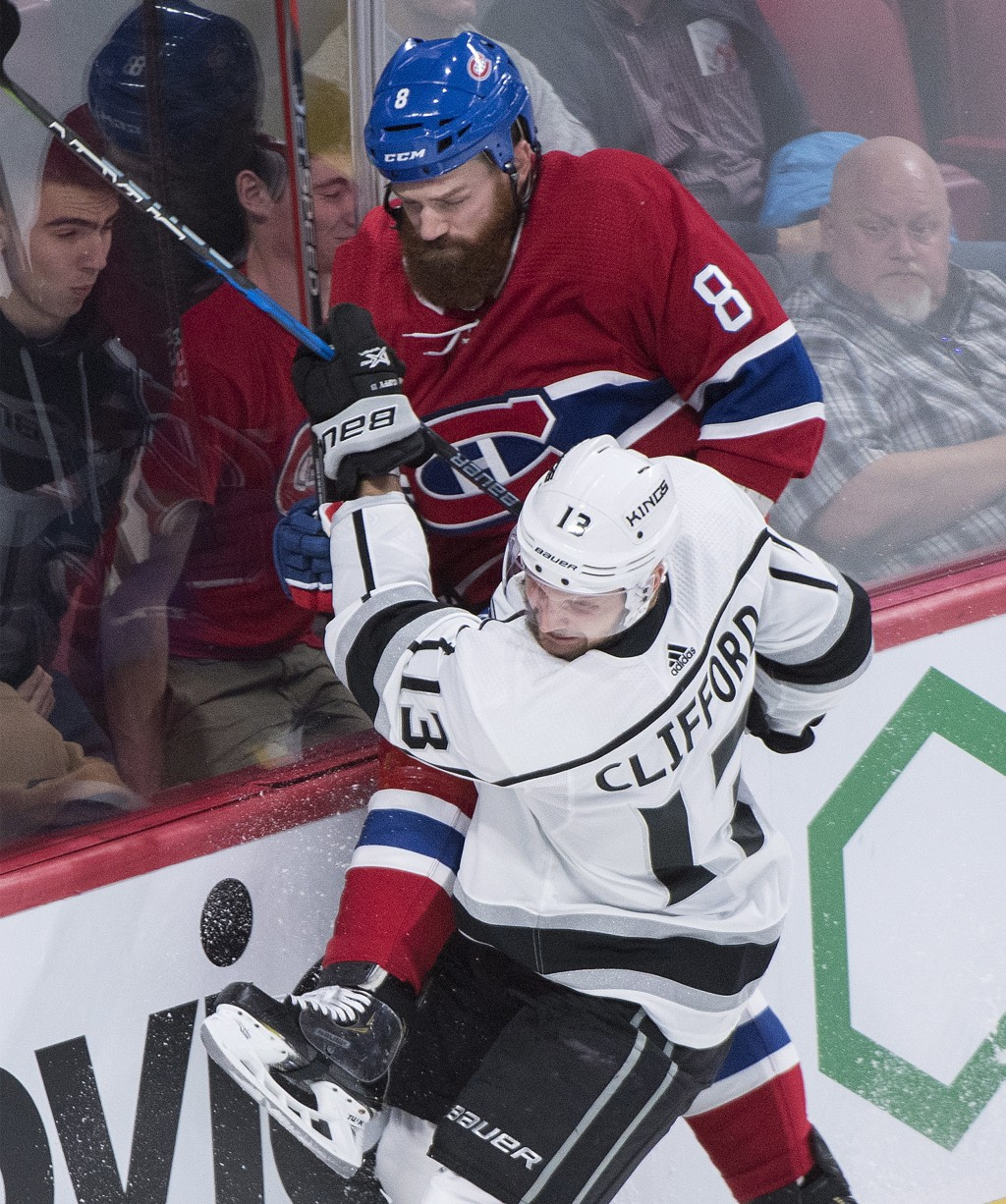 Los Angeles Kings' Kyle Clifford (13) checks Montreal Canadiens' Jordie Benn into the glass during the second period of an NHL hockey game Thursday, O