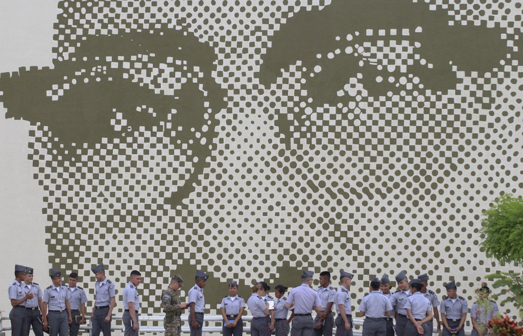 In this Oct. 3. 2018 photo, Salvadoran army cadets stand next to a huge mural of Archbishop Oscar Arnulfo Romero at the Foreign Office, in San Salvado