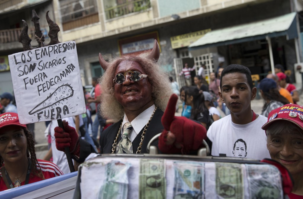 "In this Friday, Oct. 5, 2018 photo, a pro-government demonstrator dressed as a devil holds a sign with a message that reads in Spanish: ""Businessmen a"