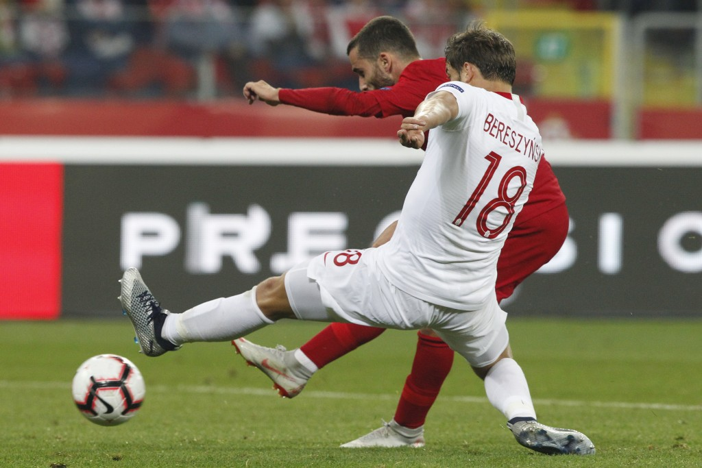 Portugal's Rafa Silva, rear, shoots as Poland's Bartosz Bereszynski tries to block the shot during the UEFA Nations League soccer match between Poland