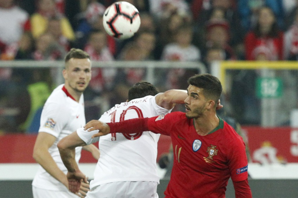 Poland's Grzegorz Krychowiak, center, hits Portugal's Andre Silva in his neck as they vie for the ball during the UEFA Nations League soccer match bet