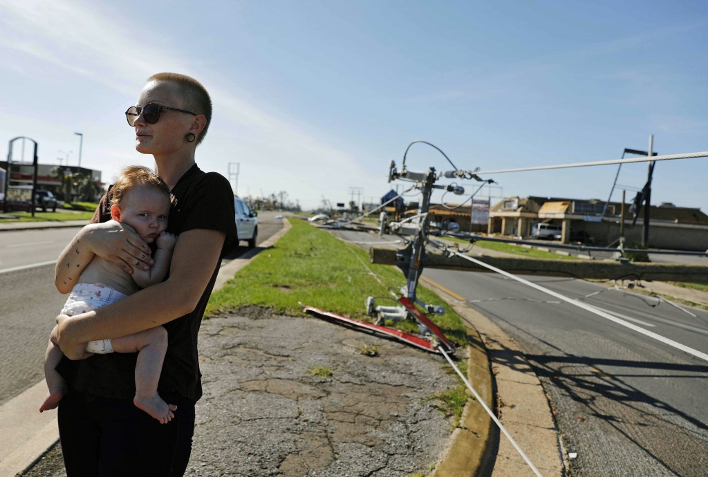 Kylie Strampe holds her four-month-old daughter, Lola, while surveying the damage from Hurricane Michael after riding out the storm in Callaway, Fla.,