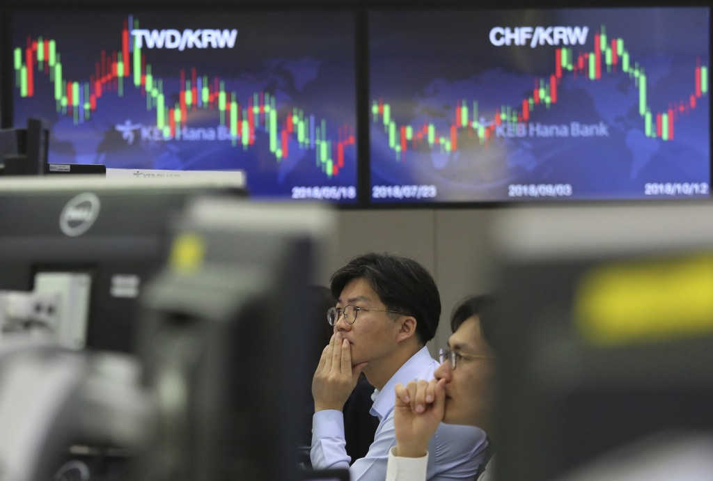 Currency traders watch monitors at the foreign exchange dealing room of the KEB Hana Bank headquarters in Seoul, South Korea, Friday, Oct. 12, 2018. A