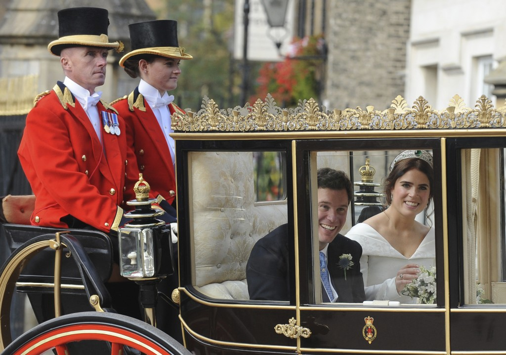 Princess Eugenie of York, right, and Jack Brooksbank smile as they travel from St George's Chapel to Windsor Castle after their wedding at St George's