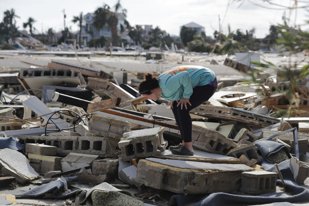Mishelle McPherson looks for her friend in the rubble of her home, since she knows she stayed behind in the home during Hurricane Michael, in Mexico B