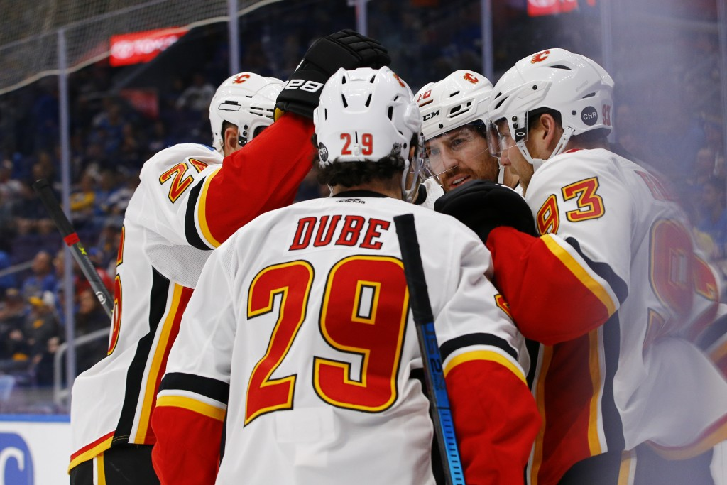 Calgary Flames' James Neal (18) is congratulated by Michael Stone (26), Dillon Dube (29), and Sam Bennett (93) after scoring a goal during the first p
