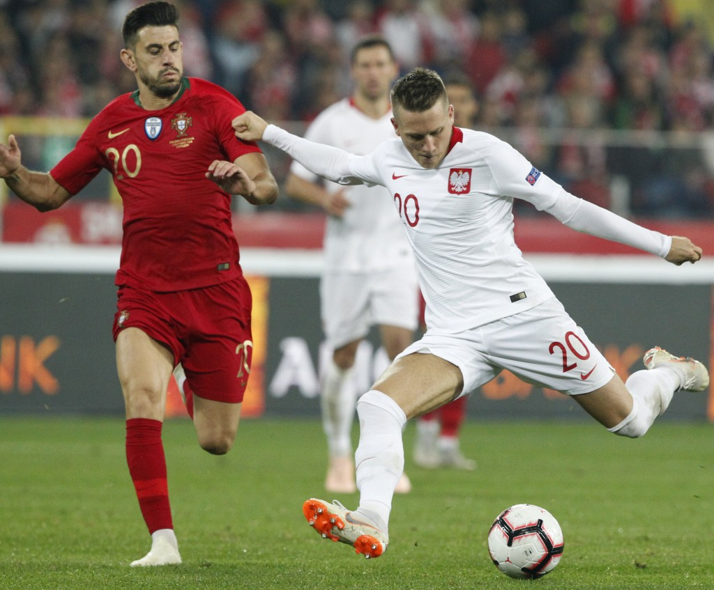 Poland's Piotr Zielinski, right, and Portugal's Pizzi vie for the ball during the UEFA Nations League soccer match between Poland and Portugal at the
