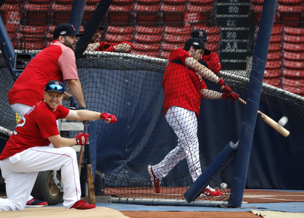 Boston Red Sox's Andrew Benintendi hits in the batting cage as teammates Mitch Moreland, left above, and Brock Holt, below, watch during a workout, Th